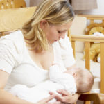 Mother Breastfeeding Baby sitting in narrow Nursery glider